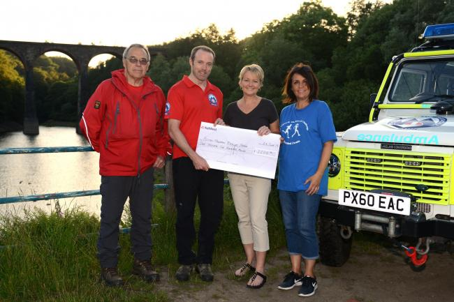 John Dickinson & Chris Greenhalgh from Bolton MRT collect a cheque from Michelle Ludwig & Tracy Gee, race directors from the Reservoir Challenge