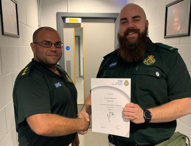 Paramedic, Jaroslaw Wierzycki is presented with a certificate and NWAS baby pin badge