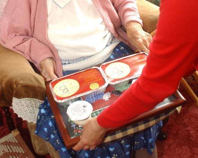 A pensioner gets the meals on wheels service.