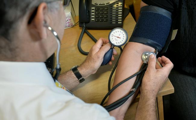 File photo dated 10/09/14 of a GP checking a patient's blood pressure. People who have high blood pressure may be twice as likely to die from Covid-19 than those without the medical condition, according to research.