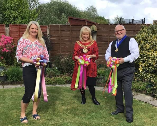 BRIGHT: Lynn Elcoat, Cllr Hilary Fairclough, and her husband Don with their bows