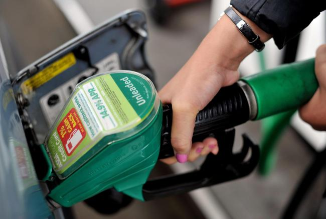 File photo dated 15/08/13 of a person using an Asda petrol pump. The supermarket has announced a price cut of 2p per litre (ppl) for petrol and diesel amid an oil war between Saudi Arabia and Russia which led to stock markets and oil prices tanking around