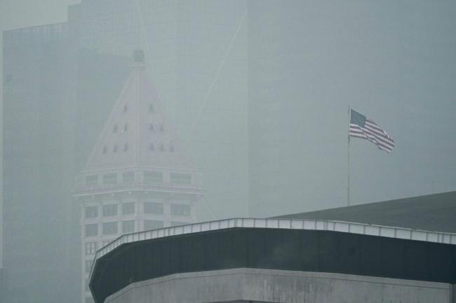 A US flag flies near Smith Tower in Seattle in air thick with smoke from wildfires