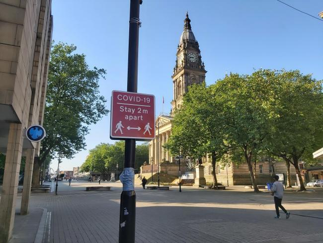 A coronavirus social distancing sign in front of Bolton Town Hall in Victoria Square