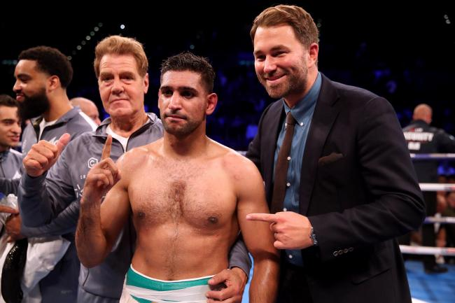 Amir Khan celebrates with trainer Joe Goossen (left) and promoter Eddie Hearn after beating Samuel Vargas on points after their Welterweight contest at Arena Birmingham, Birmingham