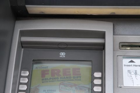 A cash machine with a plastic strip attached above the screen, containing a hidden camera. The lens hole has been circled. This is asick picture and does not show the actual device found in Farnworth.