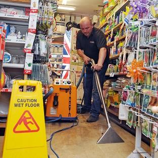 Mark Armstrong cleans the floor in Lanchester Hardware store after flooding in Lanchester, County Durham