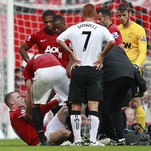 Wayne Rooney, left, receives treatment before being stretcherd off.