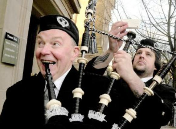 Pipe band players march on after merger