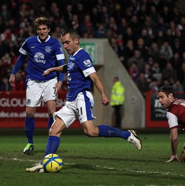 Leon Osman, centre right, fires in Everton's third goal in the FA Cup third round