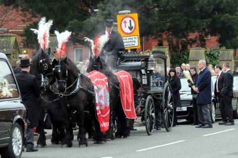 Black horses pulled the hearse containing the coffin