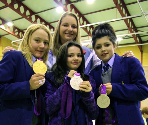 •Heather Frederiksen shares here medal collection with students, Alisha Hilton, 13, Ebony Turnbull, 12 and Kasie Hunter, 14