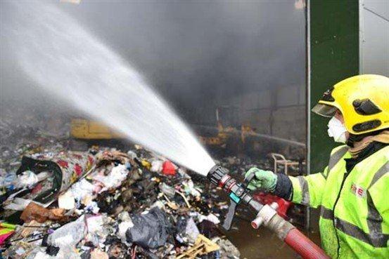 A firefighter dampens down smouldering waste.