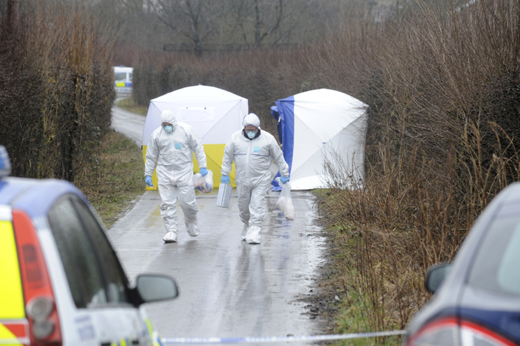 Forensic investigators in Ox Hey Lane, where a dead newborn baby was found by dog walkers