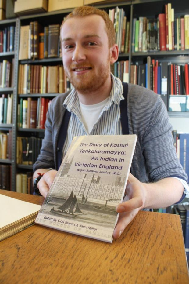 Archivist Alex Miller with a copy of  the book.