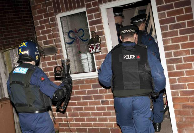 Police entering a house during the raids