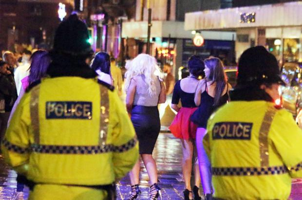 The Bolton News: Police watch revellers in Bolton town centre
