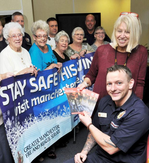 The Bolton News: Firefighter Mick Shaw with residents and home support officer Pauline Atherton
