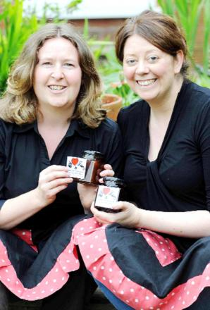 Sarah Longlands, left, and Lisa Kidd proudly display their jam and, below, pick blackberries for their business