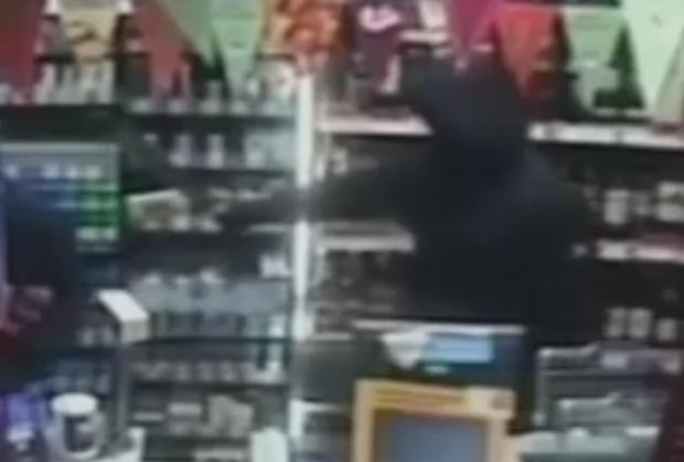 Still of machete-wielding thug caught on CCTV at Over Hulton Co-op