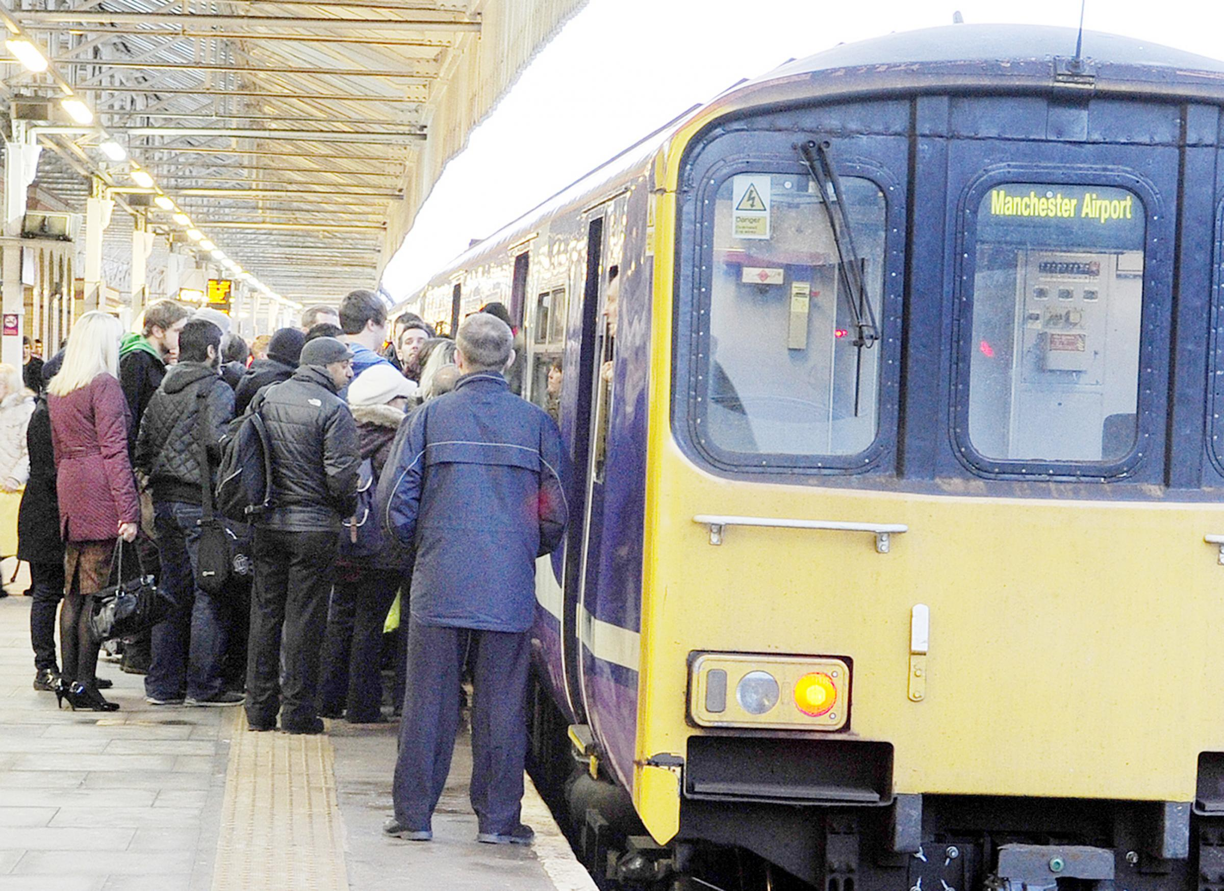 Commuters trying to get on a packed train at Bolton station last month