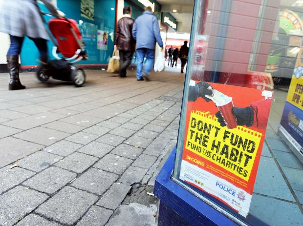 The Bolton News: A town centre poster urging people not to give cash to beggars