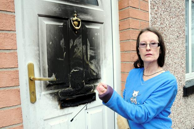 The Bolton News: Denise Hallam with the sparkler and her damaged door
