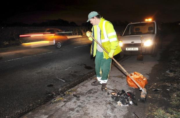 The Bolton News: A worker cleans up after the crash on the A6 in Blackrod