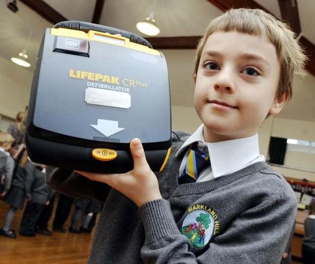 Pupil, Oliver Porteous, aged 10, with the defibrillator