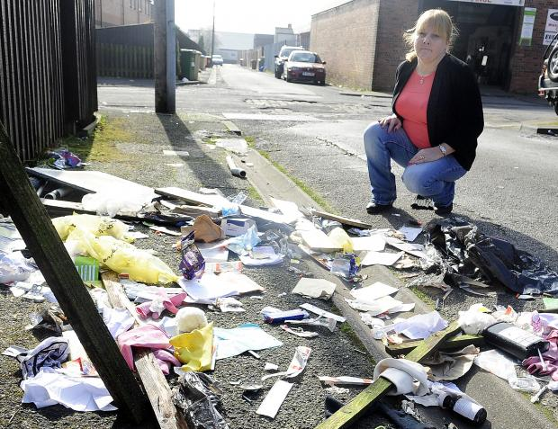 The Bolton News: Mum Nicki Ward surveys the mess left in the street,  including hypodermic syringes, needles and methadone bottles