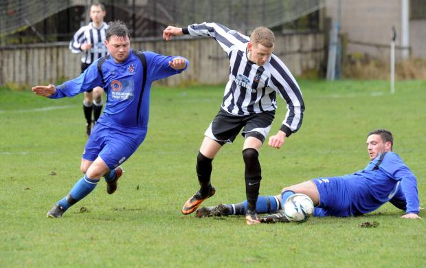 Old Boltonians' goalscorer Dean Hailwood threads a path between two Tottington pl