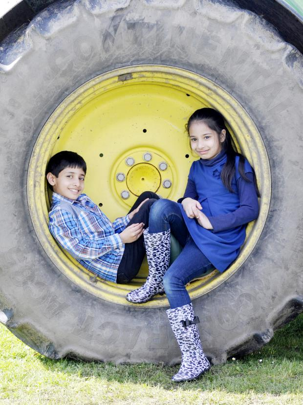 The Bolton News: Abubakr Siddiq, aged seven, and Fateema Gani, aged eight, pose in a giant tractor tyre