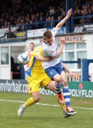 Bury's on-loan striker Danny Rose is man-handled by Exeter City's Danny Coles