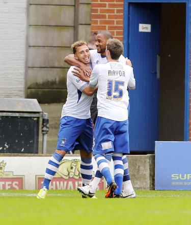 Bury's Hallam Hope, left, celebrates scoring his opener in Saturday's 4-4 draw with Portsmouth along with strike partner Clive Platt and midfielder Danny Mayor