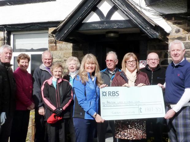 Captains Christine Studholme, and Clive Howarth present the cheque to Donna Fisk from Bolton Lads and Girls Club watched by golf club members