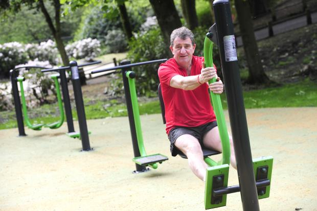 The Bolton News: Cllr John Byrne gets to grips with the new gym equipment in Queens Park, Bolton