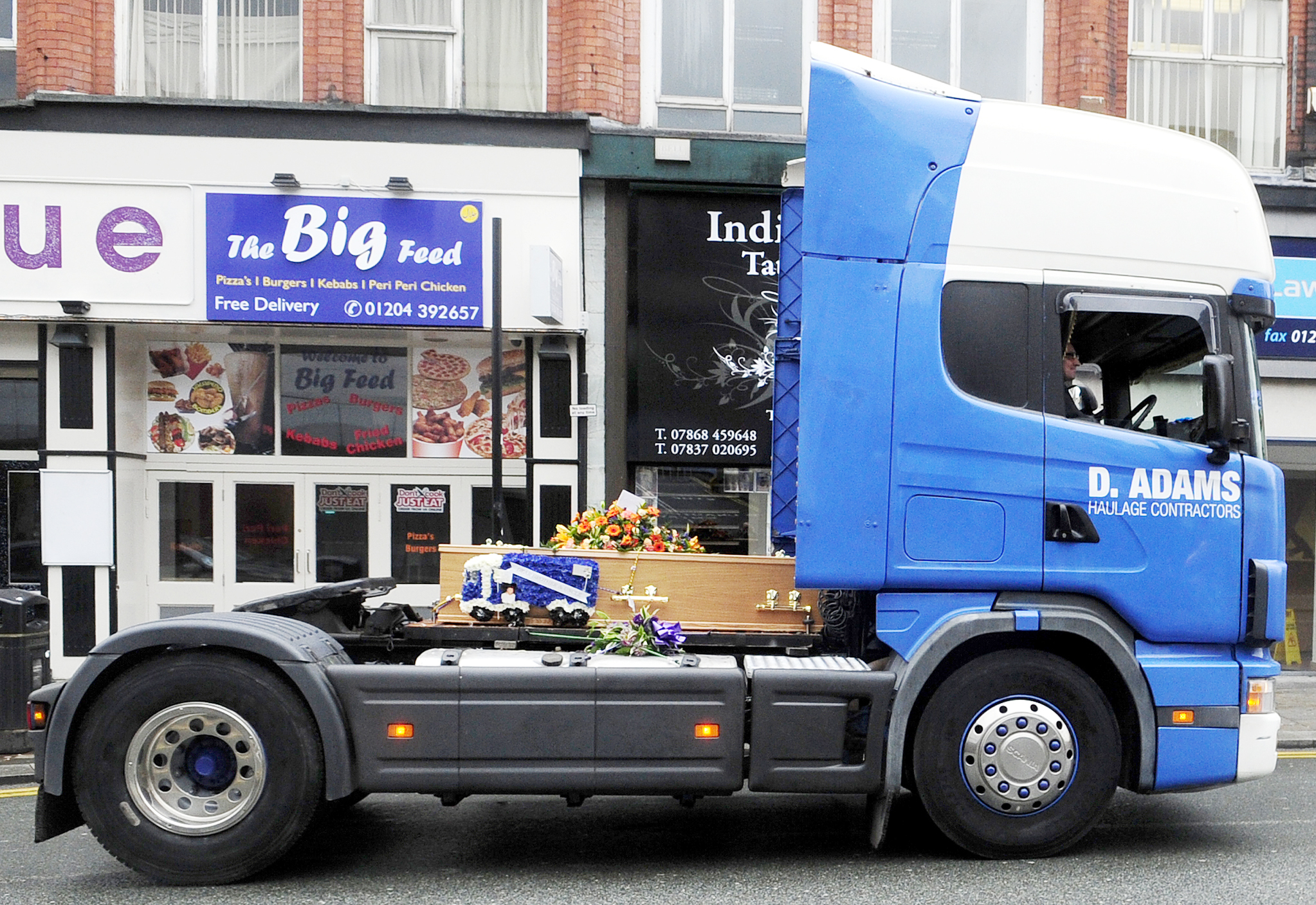 Haulage firm boss's coffin takes last ride through Bolton on the back of one of his trucks