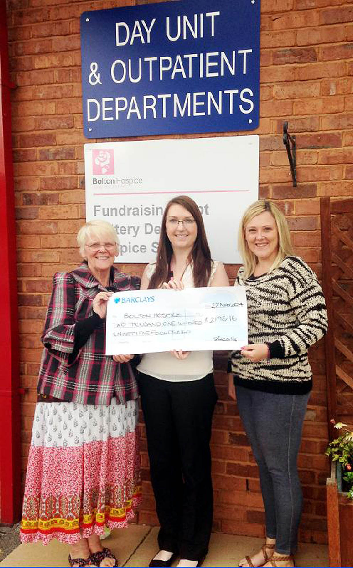 Ellen Keefe, left, and Sam Donnell, right, hand the cheque  to Stephanie Lacaille of Bolton Hospice