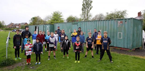 Members of Westhoughton Lions Rugby Club outside the steel containers which currently house their changing facilities