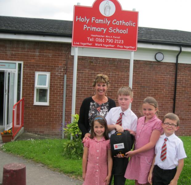 Head teacher Anne Farrell and pupils Kade Robinson, Aerin McAndrew, Isaac Jones and Kyra Hough with the defibrillator