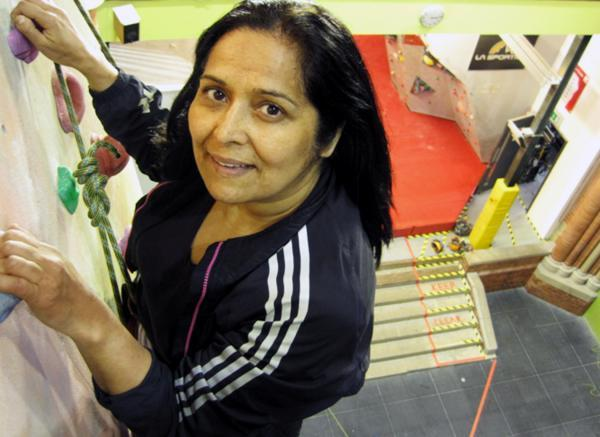 MP Yasmin Qureshi scales a climbing wall with the  British Mountaineering Climbing Council
