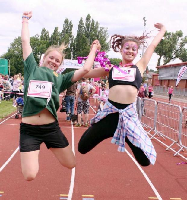 The Bolton News: Winner Nikki Reid, aged 21, left, and runner-up Frankie Connolly, aged 18, celebrate after completing the Race for Life event in Leverhulme Park.