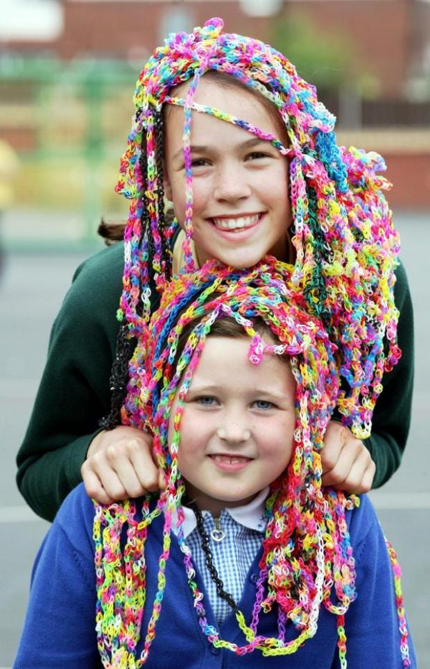The Bolton News: Ruby Jones, front, aged seven, and Lois Mawhinney, aged 10, go loom band crazy at an after-school club in Smithills, where youngsters have produced a 300-metre-long giant bracelet.