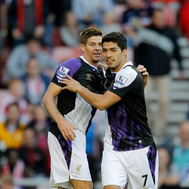 The Bolton News: Luis Suarez, right, has been hailed as outstanding, not least by Liverpool skipper Steven Gerrard, left
