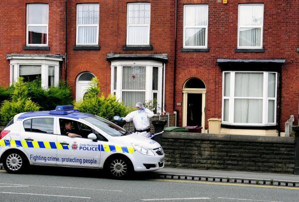 Police and forensic investigators at the house in Bolton Road, Farnworth, yesterday.