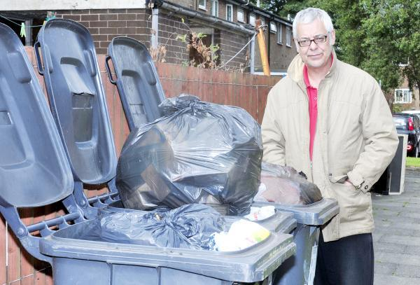 The Bolton News: Alan Gaskell from Deane, next to his overflowing bins which were not emptied during the strike