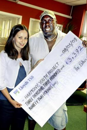 The presentation of a Gannett cheque to Charlie Barrett from the Harmony Youth Project by reporter Lucy Ewing in 2009