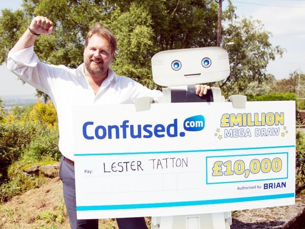 Lester Tatton receives his £10,000 cheque from Brian the Robot