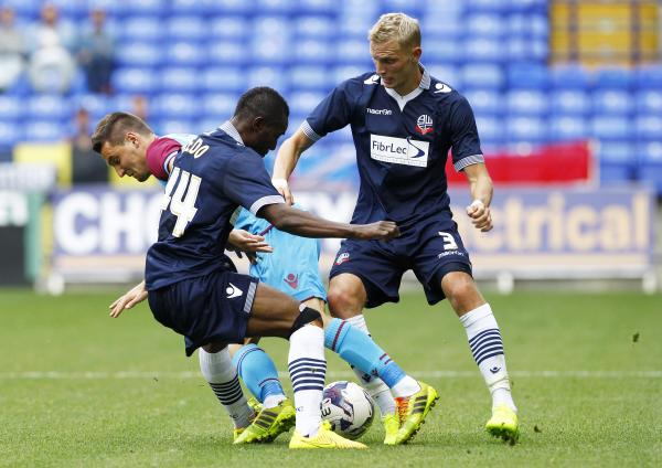 TUSSLE Dean Moxey and Medo Kamara battle to win the ball back for Wanderers