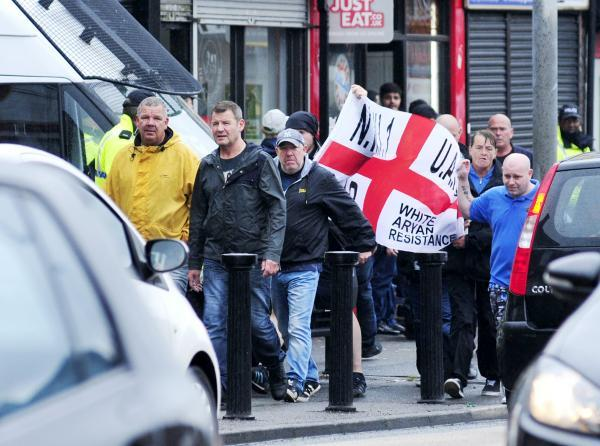 Sean Gaskell, in the yellow jacket, in front of the protesters who are carrying a North West Infidels flag